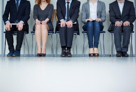 hombre sentado: Varios hombres de negocios se sientan en sillas en una fila