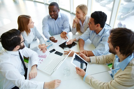 white collar: Group of business partners listening to one of colleagues at meeting