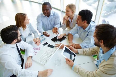 Gruppe von Geschäftspartnern zu einem Kollegen in der Sitzung zu hören