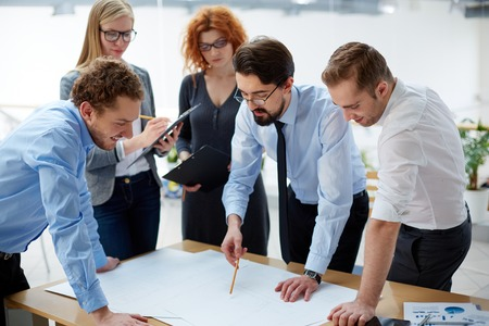 female engineer: Team of engineers discussing blueprint at meeting Stock Photo