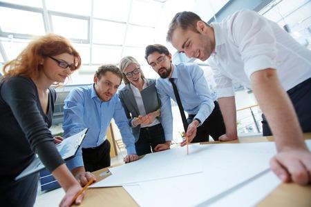 Team van ingenieurs bespreken blauwdruk op de vergadering