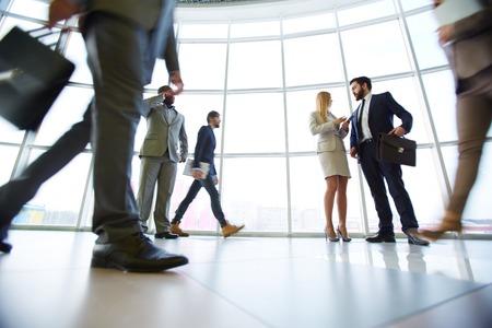 Bedienden te communiceren in het kantoor tegen venster met hun collega's rond te lopen Stockfoto