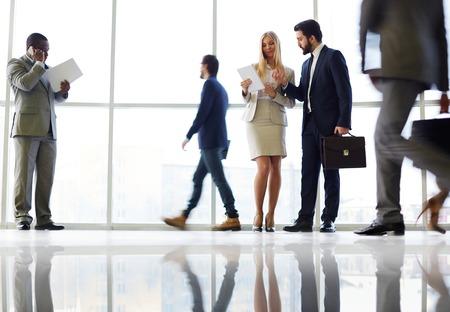 persona caminando: Los trabajadores de cuello blanco la comunicación en la oficina contra la ventana con sus colegas caminando