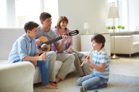 Portrait of handsome siblings and their father playing musical instruments at home photo