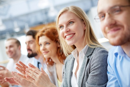 Closeup image of a smiley business leader clapping at the seminar with her team on the foreground