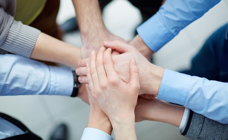 joined hands: Above view of business partners making a pile of hands  Stock Photo