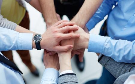 manos unidas: Los empresarios unen sus manos en el signo de la unidad