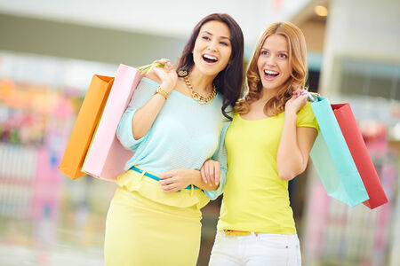 astonished: Portrait of surprised girls in smart casual with paperbags expressing astonishment