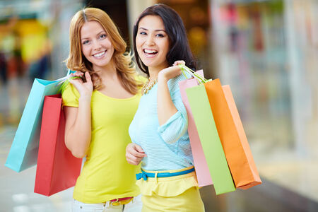lifestyle looking lovely: Portrait of two happy girls with paperbags looking at camera Stock Photo