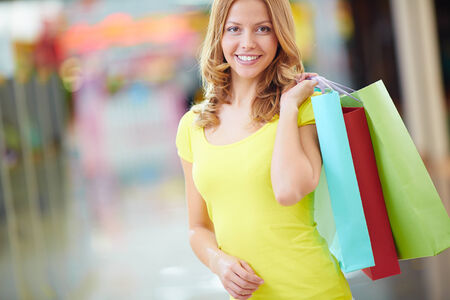 shopaholism: Portrait of happy girl holding colorful shopping bags