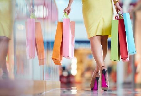 personal shopper: Legs of shopaholic with shopping bags walking down mall
