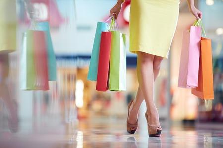 Benen van shopaholic met boodschappentassen lopen naar beneden mall