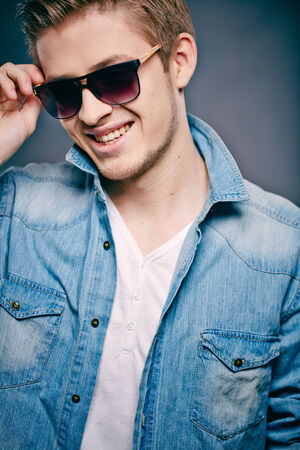A young guy in sunglasses posing in front of camera photo