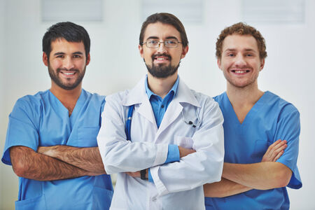 Portrait of three successful clinicians in uniform looking at camera photo