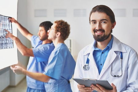 Portrait of friendly doctor looking at camera on background of his colleagues interacting photo