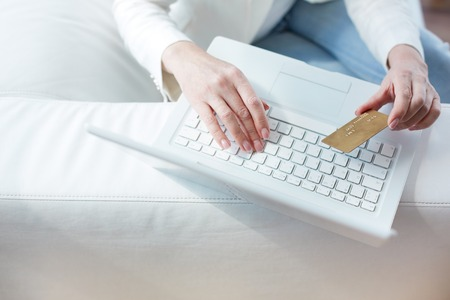 Hands of female sitting at the laptop with a credit card photo