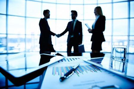 technology agreement: Technological devices, financial document with pen, glass of water at workplace on background of three business partners striking deal
