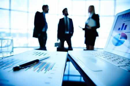 ノート パソコンと対話する 3 つのビジネス パートナーの背景に職場でペンで金融ドキュメント