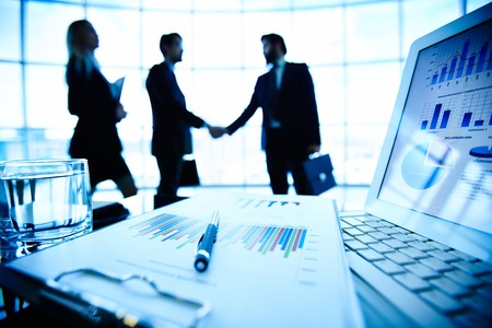 Laptop, financieel document met pen en glas water op de werkplek op de achtergrond van drie business partners maken van een deal Stockfoto