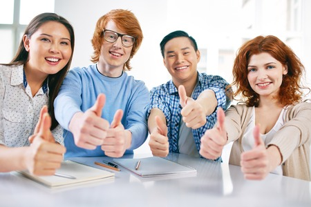 Company of smart groupmates looking at camera and showing thumbs up Stock Photo