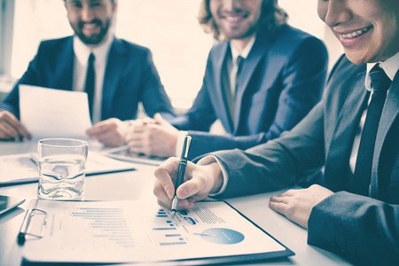 analyzed: Closeup of graphs and chart analyzed by smiling business people Stock Photo