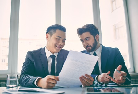 persuading: Two managers discussing contract in meeting room