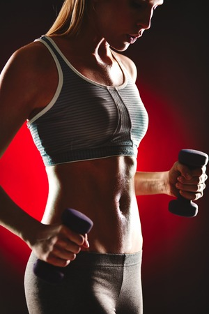 activewear: Image of slim female in activewear doing exercise with dumbbells