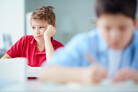 reluctant: Portrait of bored schoolboy sitting at lesson