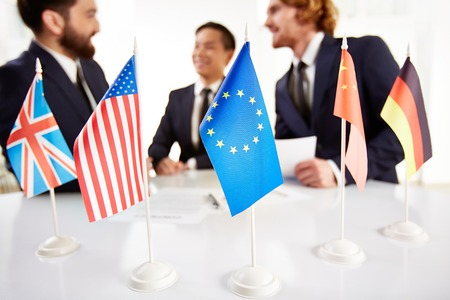 talks: Image of several flags of different countries on workplace with three partners negotiating on