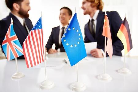 conversaciones: Imagen de varias banderas de diferentes países en el lugar de trabajo con tres interlocutores en las negociaciones sobre Foto de archivo
