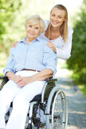 Pretty nurse and senior patient in a wheelchair looking at camera photo