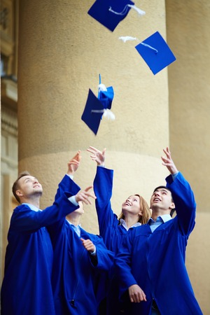 alumna: Group of smart students in graduation gowns throwing their hats Stock Photo