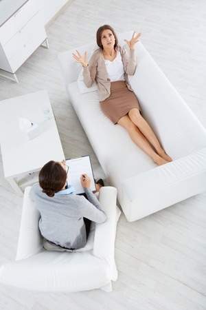 counseling session: Above view of attentive psychiatrist listening to female patient in clinic