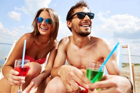 jovenes enamorados: Jóvenes amantes relajado con bebidas que tiene fiesta en la playa Foto de archivo