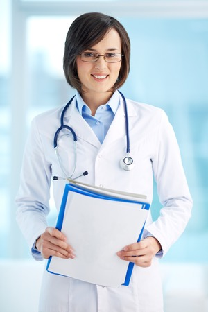 general practitioner: Vertical portrait of a lovely general practitioner holding documents