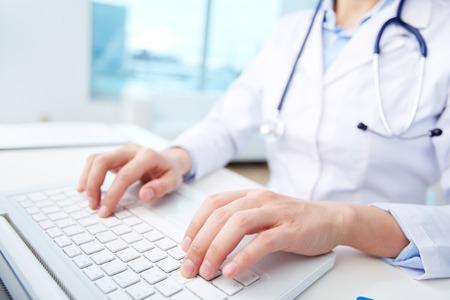usando computadora: Primer plano de un trabajador m�dico escribiendo en la computadora port�til
