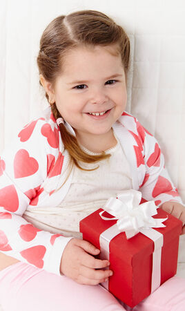 Portrait of happy girl with giftbox looking at camera and smiling    photo