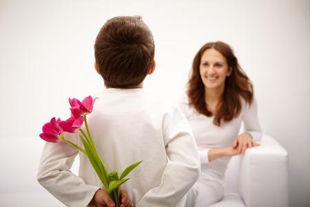 gar�on souriant: Vue arri�re de jeune gar�on avec un bouquet de belles tulipes dans le dos de la pr�paration belle surprise pour sa m�re Banque d'images