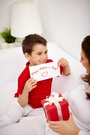 mother s day: Cute lad with congratulating card looking at his mother with giftbox
