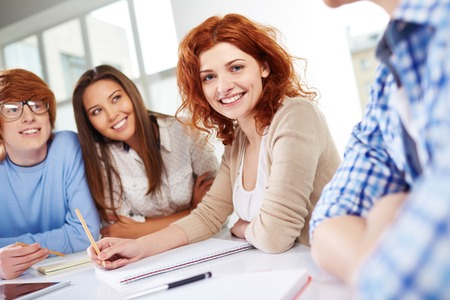 focus group: Group of smart groupmates sitting at lesson, focus on happy girl Stock Photo