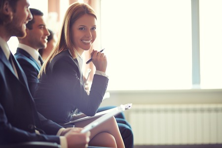 success focus: Row of business people sitting at seminar, focus on attentive young female