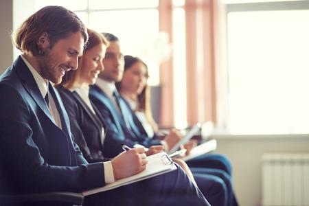 Rij van mensen uit het bedrijfsleven het maken van notities op seminar met jonge man op de voorgrond Stockfoto