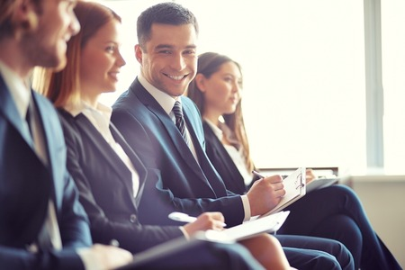 curso de formacion: Fila de gente de negocios haciendo notas en el seminario con el foco en la sonrisa joven