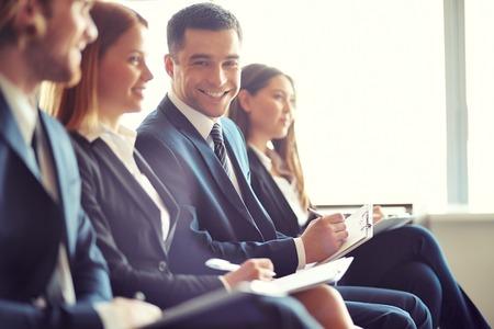Rij van mensen uit het bedrijfsleven maken van aantekeningen tijdens seminar met focus op lachende jonge man