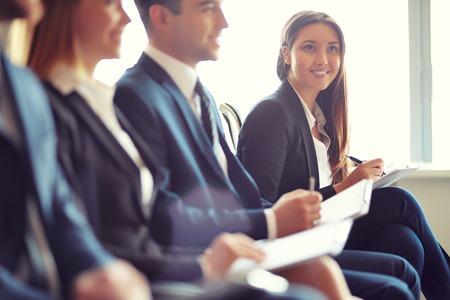 Rij van mensen uit het bedrijfsleven zitten aan seminar, gericht op attente jonge vrouwelijke
