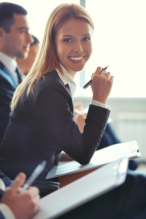 Smiling businesswoman looking at camera at seminar with her colleagues near by photo