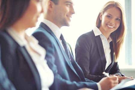 curso de capacitacion: Empresaria sonriente mirando a la cámara en el seminario con sus colegas cerca por Foto de archivo