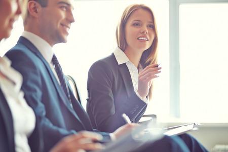 empleados trabajando: Empresaria inteligente que hace la pregunta en el seminario con sus colegas en las inmediaciones