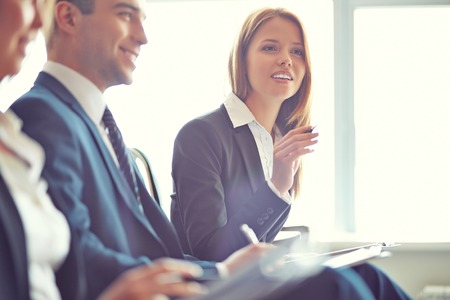 executive courses: Smart businesswoman asking question at seminar with her colleagues near by Stock Photo
