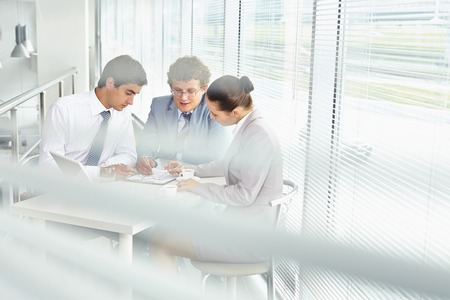 Three business people discussing statistics in office Stock Photo - 27662944